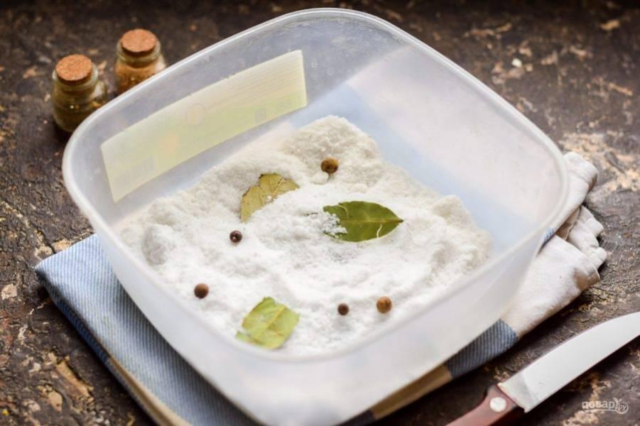 После возьмите удобный контейнер, в котором будет солиться сало. Всыпьте в контейнер половину порции соли, добавьте лаврушку и перцы.