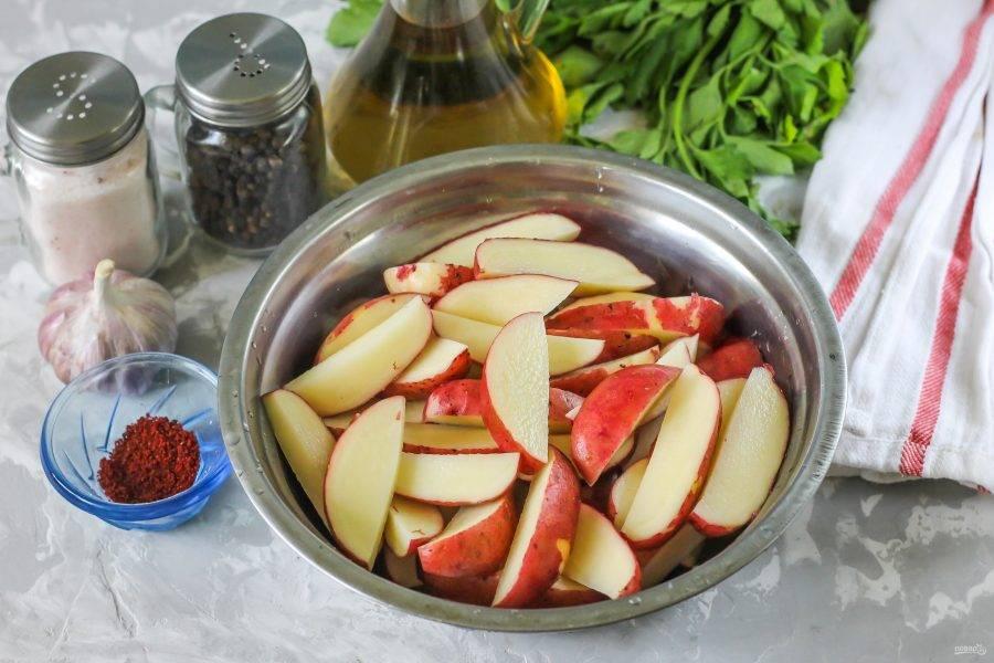 Картофельные клубни промойте в воде с помощью губки, бережно счищая кожуру от грязи и пыли. Затем разрежьте каждый корнеплод пополам и нарежьте ломтиками в миску или в салатник.