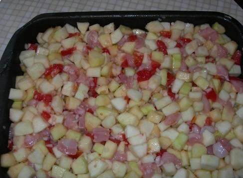 Выкладываем на противень кабачки, филе, помидоры и лук. Перемешиваем и солим.