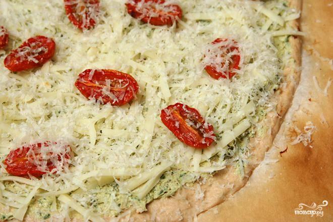 3. Посыпать тертым сыром Моцарелла, выложить помидоры и посыпать тертым Пармезаном. Выложить пиццу на камень для пиццы вместе с пергаментной бумагой. Выпекать 8-10 минут, пока корочка не потемнеет по краям.