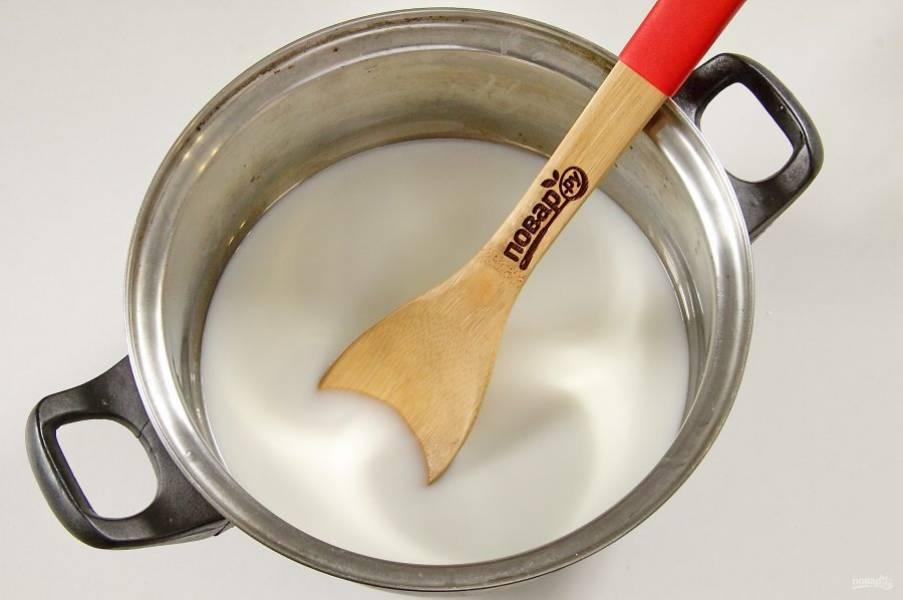 Добавьте молоко и воду в равных пропорциях. Перемешайте, доведите до кипения и варите кашу до готовности на небольшом огне, периодически помешивая.