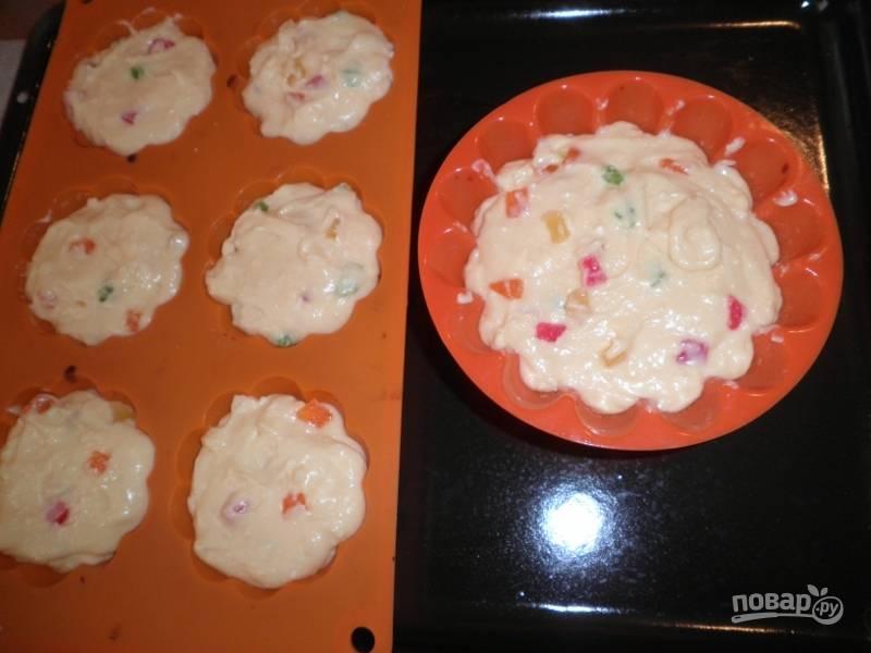 Я выбираю разноцветные цукаты в сахарной пудре. Вмешиваю их в тесто, промазываю формочки для кексов маслом, вливаю тесто. Греем духовку до 180 градусов, ставим туда куличи и печем примерно 45-50 минут.