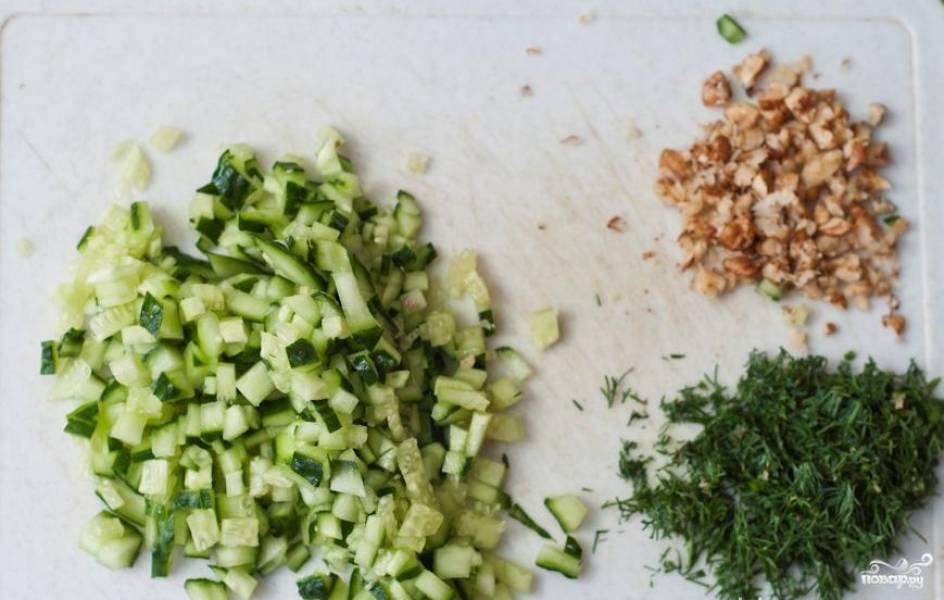 Огурцы режем мелкими кубиками, грецкие орехи размельчаем при помощи блендера, укроп мелко рубим.