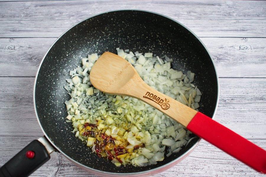 На разогретом оливковом масле пассеруйте измельченные лук и чеснок, зиру, хлопья острого перца. Готовьте до прозрачности лука.
