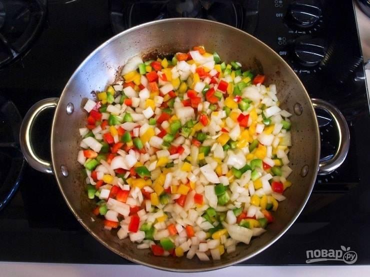 2. Затем мясо уберите, а на его место выложите мелко нашинкованный белый репчатый лук и перец. Тушите овощи 5 минут, иногда помешивая.