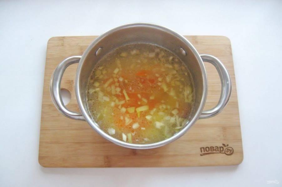 После добавьте лук и морковь в кастрюлю.