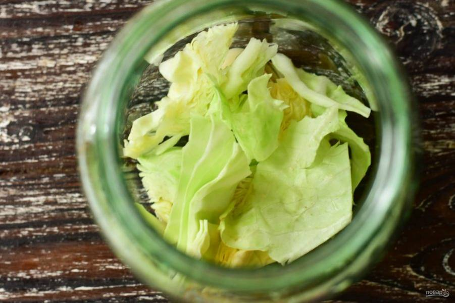 Затем выложите большую часть нарезанной капусты.
