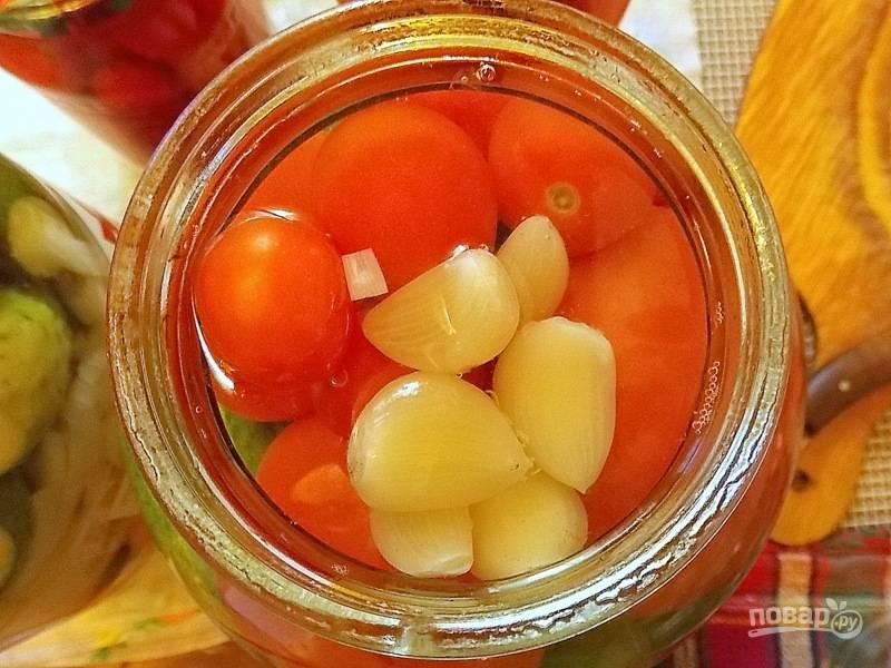 Выложите чеснок и залейте овощи кипятком до верху. Прикройте крышкой, оставьте на 20 минут.