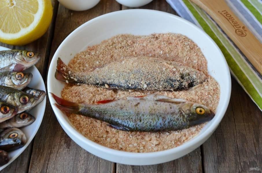 Разогрейте рафинированное масло в сковороде. Маринованную рыбку панируйте в смеси сухарей и кунжута.