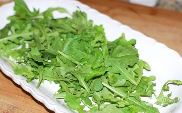 4. На тарелку для подачи выложите рукколу или другую зелень, предварительно вымыв и обсушив. Сверху выложите авокадо и полейте соком лимона.