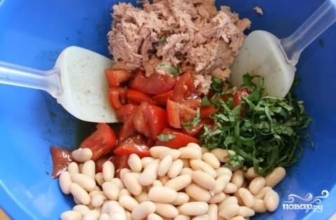 В салатнице смешайте фасоль, тунец, крупно нарезанные помидоры, зелень и заправку. Посолите и перемешайте.