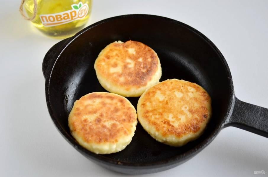 6. На горячую сковороду, смазанную маслом, выкладываем сырники и жарим до корочки. Огонь должен быть средний, переворачивайте сырники, жарьте.