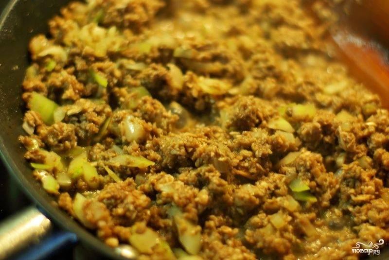 Грибы добавляем к луку на сковородку и обжариваем их, пока полностью не выкипит жидкость из грибов.