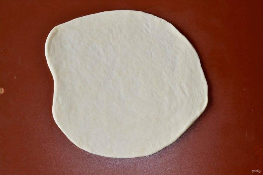 Отщипните кусочек теста и раскатайте тонким пластом.