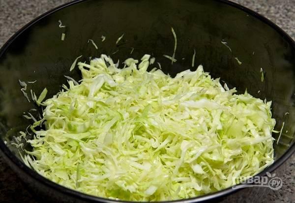 3. А пока варится курочка, можно заняться капустой. Вымойте, обсушите и нашинкуйте половину средней капусты. Если она уже довольно плотная (не молодая), то помните ее как следует руками.