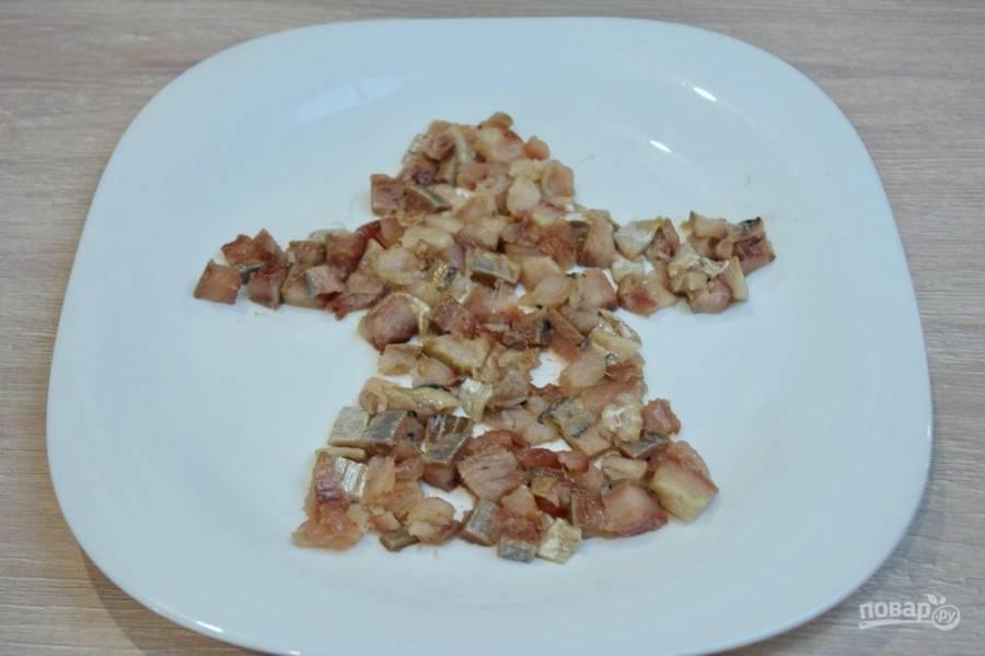 Для приготовления салата очистите селедку привычным способом. Хвостик и голову сохраните целыми. Мякоть нарежьте мелко кубиком. Уложите на плоское широкое блюдо селедку как показано на фото.
