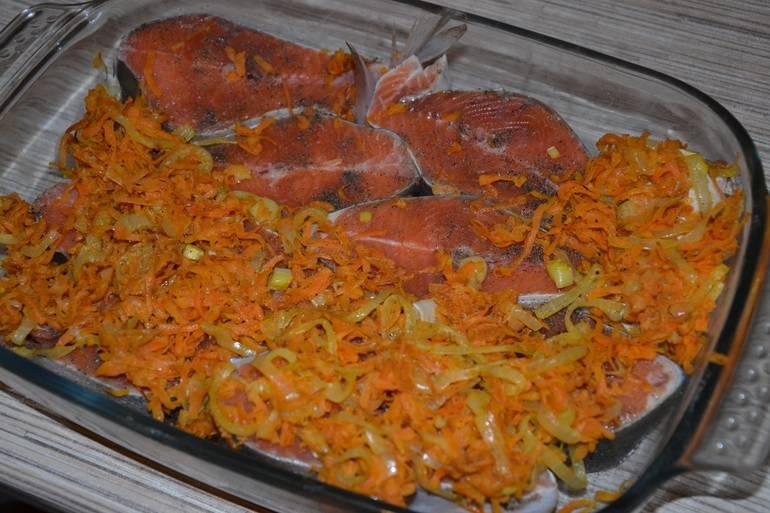 Промаринованную горбушу выкладываем в форму для запекания, сверху кладем обжаренные на растительном масле морковь и репчатый лук.