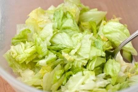 Салат помойте, просушите и порвите на небольшие кусочки.