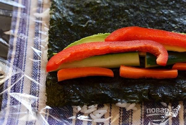 6. Еще один вариант — выложить на пленку рис, а сверху положить лист нори. Затем начинку.