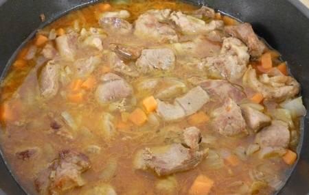 Выкладываем овощи к мясу и обжариваем 4-5 минут. Добавляем бульон и томатную пасту, соль по вкусу. Перемешиваем и доводим все до кипения. Тушим на медленном огне, под крышкой, примерно 40-45 минут. За несколько минут до конца добавьте лавровый лист и измельченный чеснок.