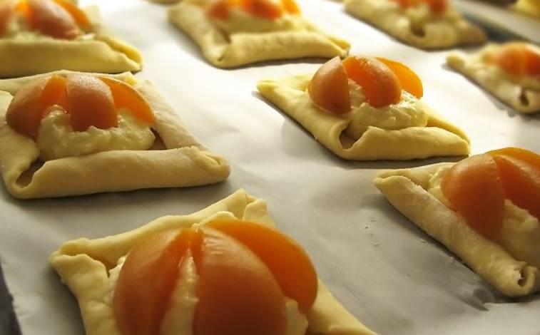 Наполняем тесто начинкой и добавляем консервированные абрикосы, порезанные дольками.