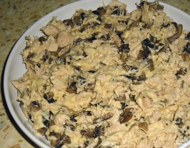 В отдельной пиалке соедините поджаренные с луком и чесноком грибочки и отварную грудку. Добавьте к ним сливочный сыр и хорошенько все перемешайте. Сливочный сыр можно заменить на обычный твердый, натертый на терке.