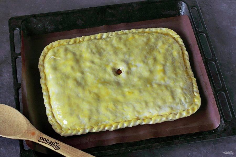 Накройте начинку вторым пластом и защипните края любым удобным способом. Сделайте по центру дырочку для выхода пара и смажьте поверхность желтком. Выпекайте в духовке при температуре 190 градусов около 45 минут. Во время выпекания пару раз откройте духовку и сбрызнете стенки водой из распылителя.