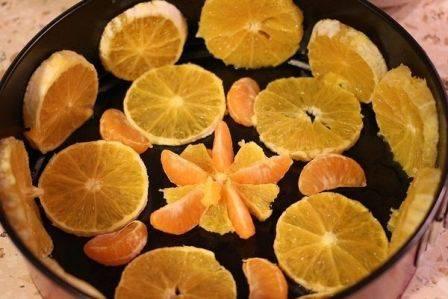 Дно формы выстилаем пищевой пленкой и красивы раскладываем подготовленные фрукты.