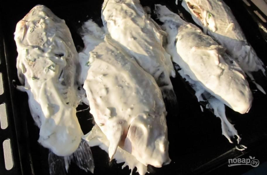 3. Теперь обильно смажем сметаной каждую рыбку, посыпаем сверху немного солью и отправляем запекаться в духовке при температуре в 160 градусов на 40 минут.