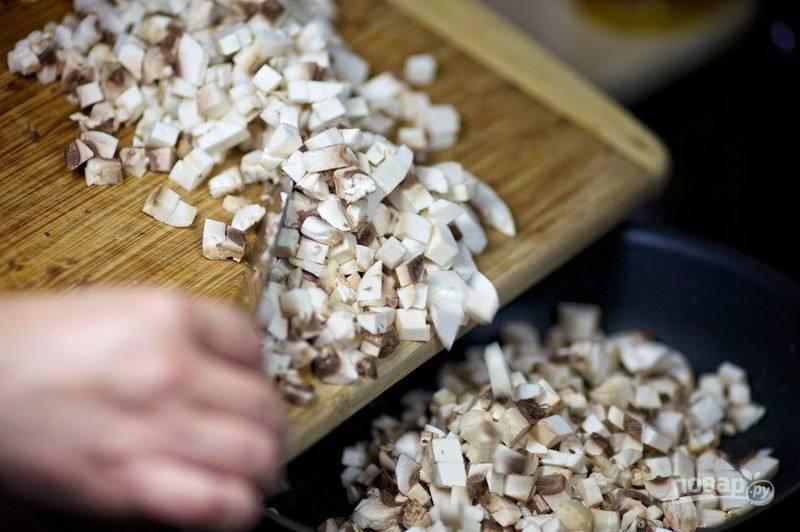Промойте и нарежьте мелкими кубиками грибы, выложите в разогретую с маслом сковороду и обжарьте.