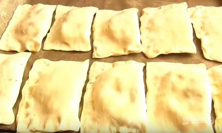 6. В центр каждого прямоугольника выложите начинку, сложите пополам и защипните. Получится пирожок в виде конверта. Выложите их на пергамент, смазанный растительным маслом. Смажьте им и пирожки.