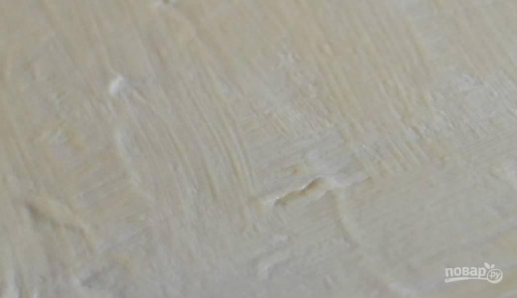 Слоено-дрожжевое тесто разморозьте и раскатайте в тонкий пласт, присыпая рабочую поверхность мукой. Достаньте из холодильника сливочное масло, дайте ему немного постоять при комнатной температуре, чтобы оно подтаяло. Смажьте маслом поверхность раскатанного теста.