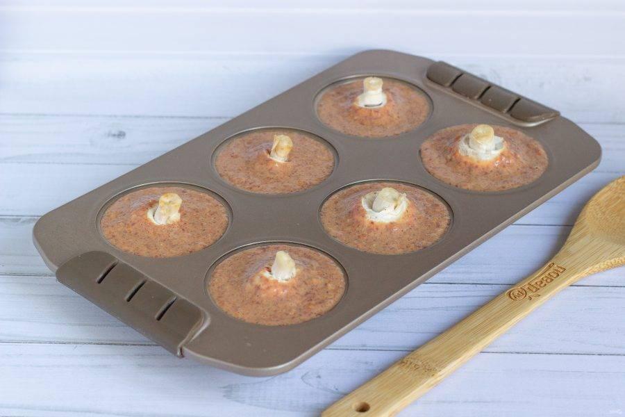 """Разложите печеночную массу по формам для кексов, предварительно смазанных растительным маслом. В каждую формочку """"утопите"""" чистый шапиньон. Запекайте суфле 25-30 минут при температуре 180 градусов."""