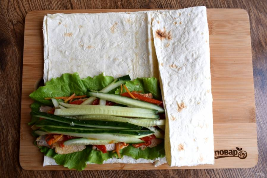 Лаваш смажьте соусом из йогурта и измельченного чеснока. Положите листья салата и все остальные ингредиенты. Заверните нижний край лаваша на начинку.