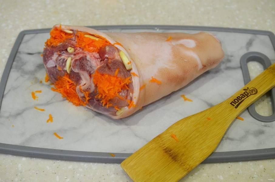 3. Рульку посолите, поперчите. В углубления вставьте морковь и чеснок.