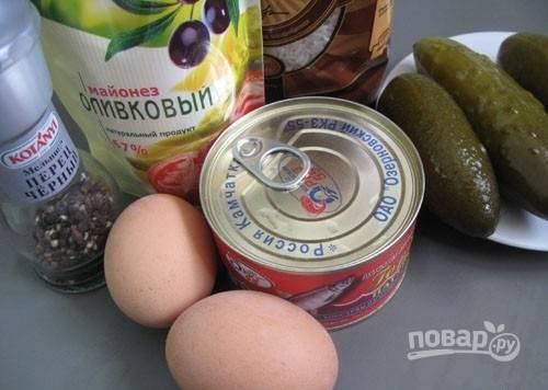 1. Первым делом поставьте вариться рис в подсоленной воде. Яйца отварите вкрутую. Консервированную рыбку переложите в глубокую мисочку и разомните вилкой.