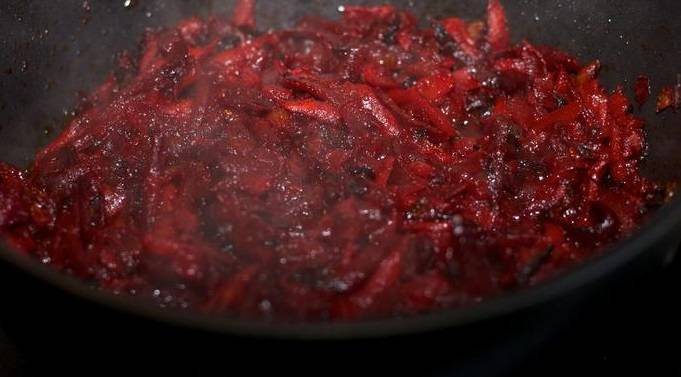 Разогрейте на сковороде растительное масло. Обжарьте в нем лук, затем добавьте свеклу и морковь. Тушим все под крышкой 20-25 минут. Когда овощи станут мягкими, добавляем томатную пасту и 1 ст.л. лимонного сока. Тушим еще 5 минут.