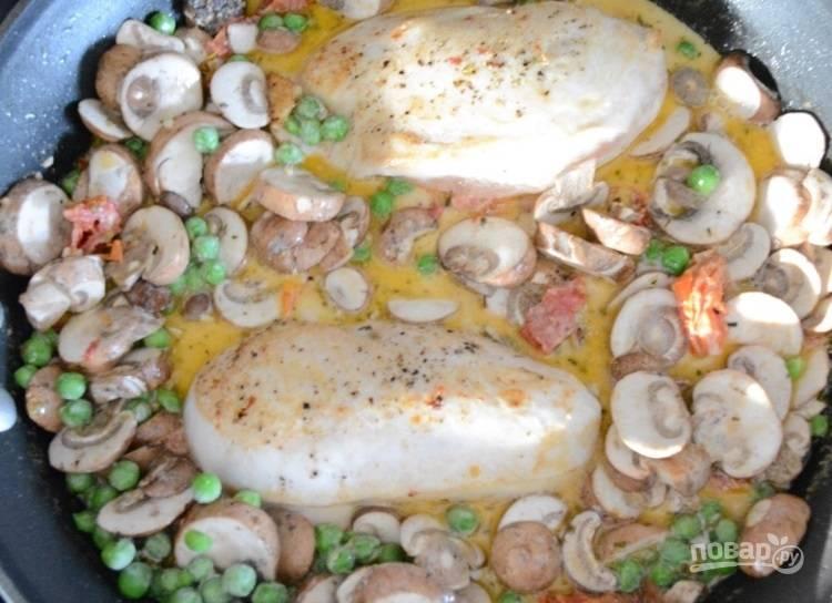 5.Верните в сковороду куриные грудки, добавьте нарезанные пластинками грибы и горошек.