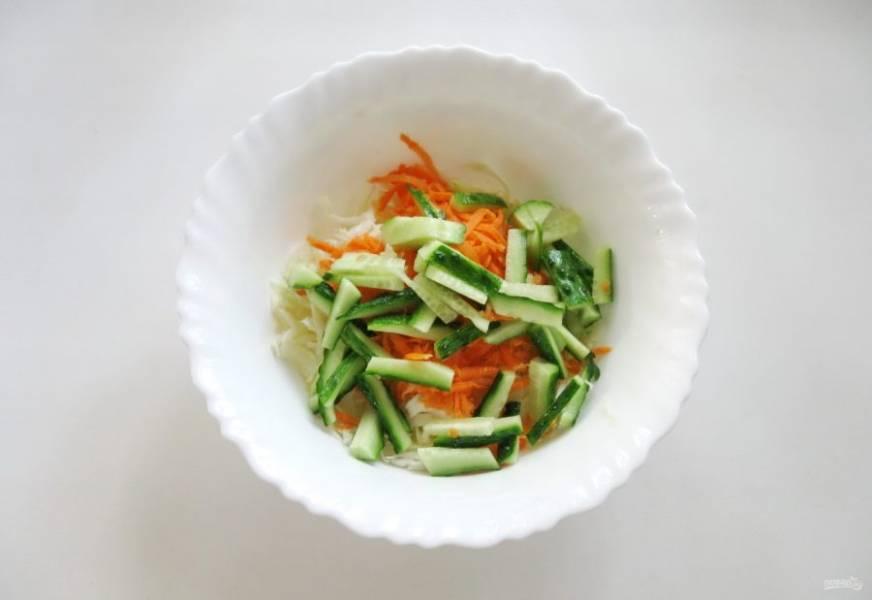 Свежий огурец помойте и нарежьте соломкой. Выложите в салатник.