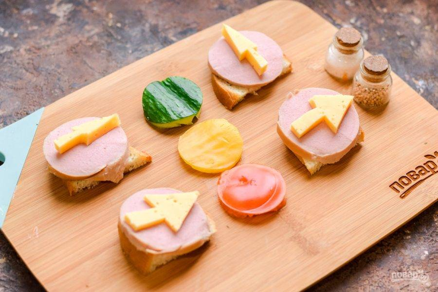 Из твердого сыра вырежьте острым ножом дорожные знаки, стрелочки, которые регулируют движение, разложите их поверх колбасы.