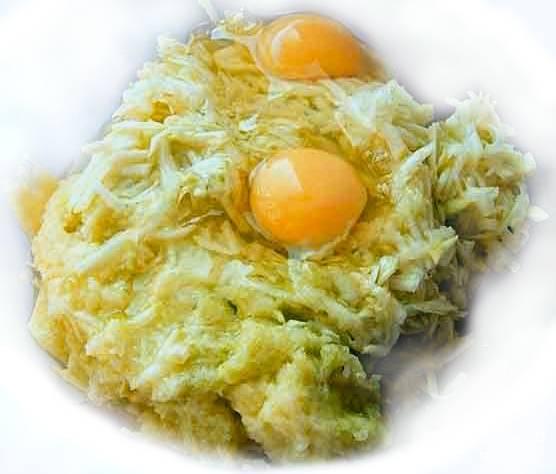 Чистим картофель. Трем его на крупной терке. Можете воспользоваться кухонным комбайном, выставив режим крупной терки. Разбиваем пару яиц в картофельную массу.