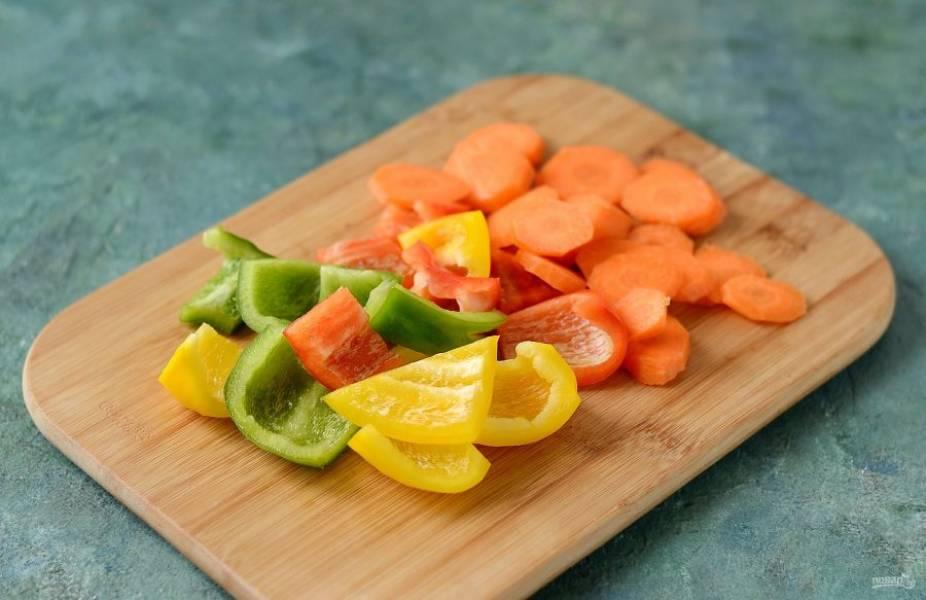 Перцы помойте, удалите хвостики и семена. Нарежьте на крупные ломтики. Морковь очистите, нарежьте кружочками.
