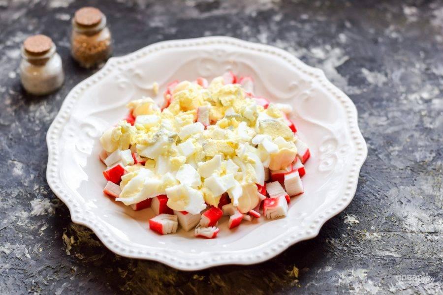 Куриные яйца отварите вкрутую, почистите. Нарежьте яйца мелкими кубиками и выложите поверх палочек. Смажьте майонезом. Соль и перец добавляйте по вкусу.