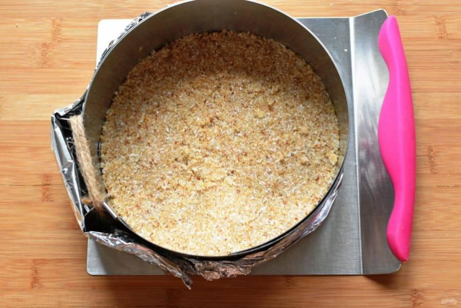 Выложите смесь ровным слоем на дно разъемной формы для торта, хорошо уплотните с помощью донышка стакана и уберите в морозилку на 20 минут.