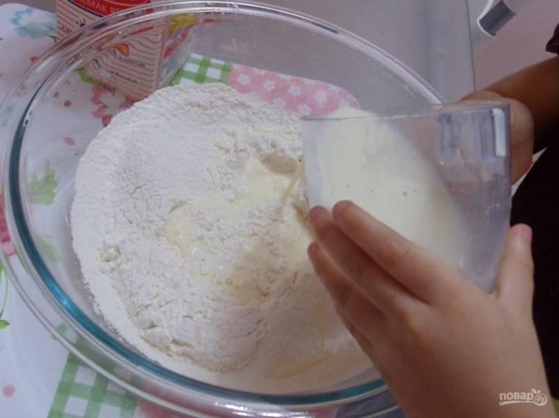 2.В центре сухой смеси сделайте углубление, туда вбейте куриные яйца, влейте молоко и половину воды.