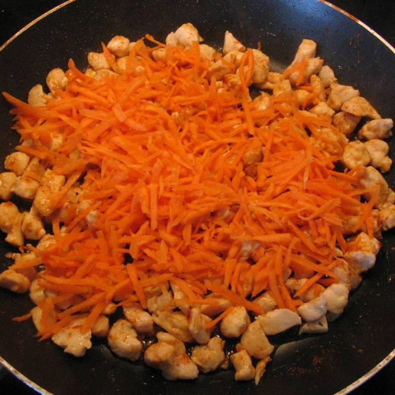 Добавить натёртую морковь к курице и перемешать. Поставить на медленный огонь и жарить 5-10 минут.