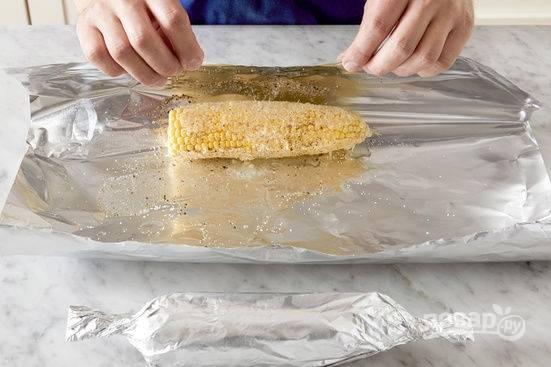 3.Смешайте мягкое сливочное масло с чесноком, каждую кукурузу смажьте чесночным маслом, посолите и поперчите, оберните каждый початок в отдельный отрез фольги и добавьте по столовой ложке воды. Отправьте в разогретый до 200 градусов духовой шкаф на 15 минут.