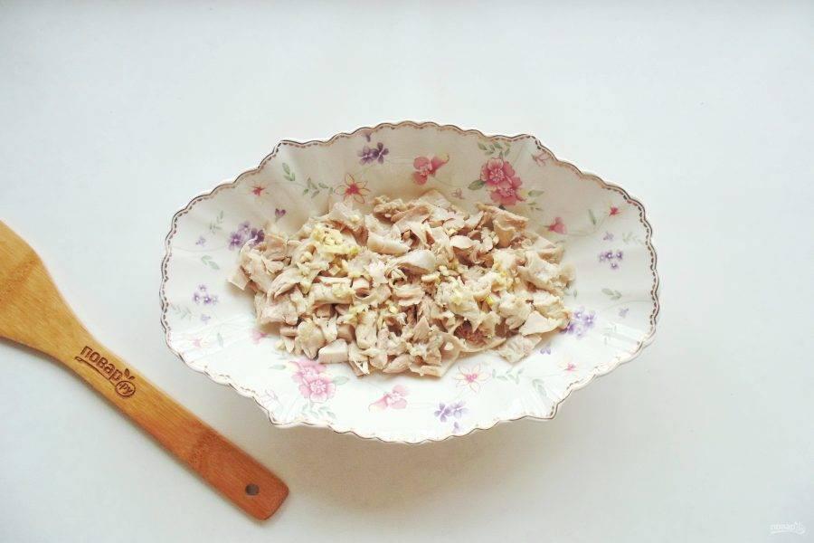 Курицу мелко нарежьте и разложите по тарелкам. Добавьте измельченный чеснок.