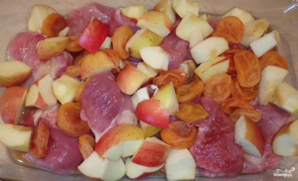 Промываем яблоки и курагу. Яблоки очищаем от сердцевины и семечек, нарезаем кубиками. Добавляем все в форму для запекания.