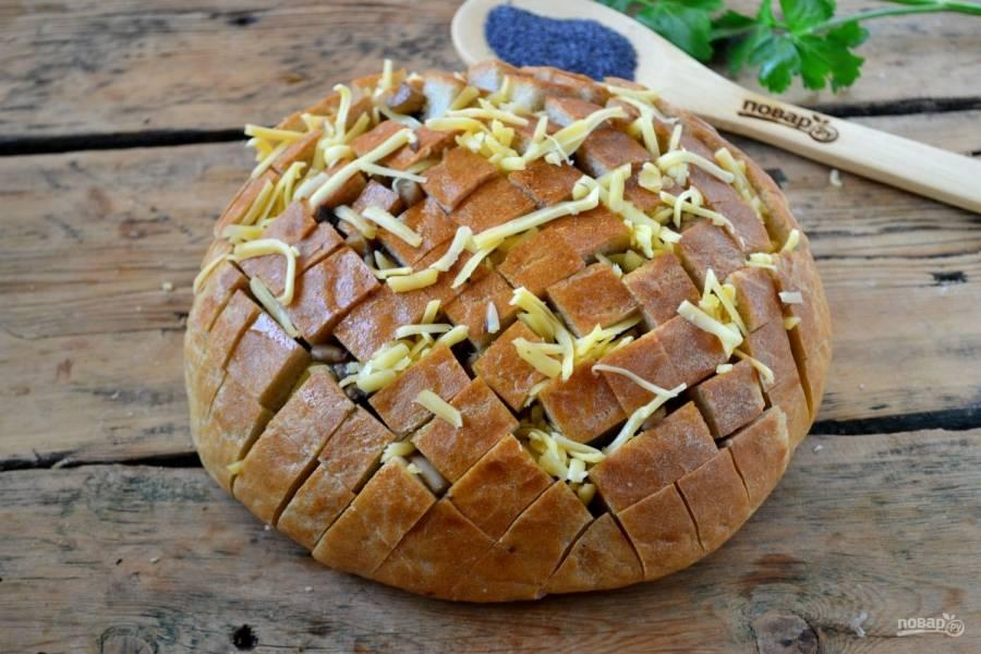 Поверх грибов выложите тертый сыр, старайтесь вкладывать его именно в разрезы.
